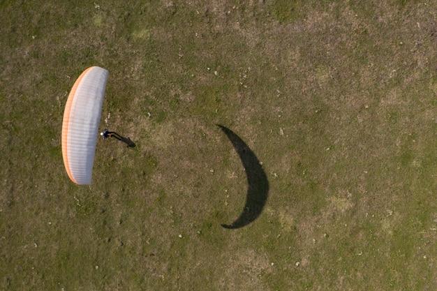 Paraglider draufsicht, er lernt auf einem flugzeugfeld zu fliegen.
