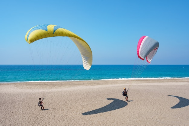 Paraglider tandem fliegt über die küste mit blauem wasser und himmel auf horison. ansicht des gleitschirms und der blauen lagune in der türkei.