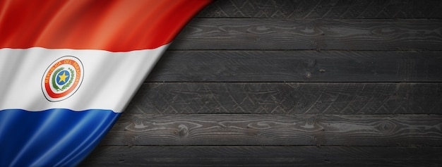 Paraguay flagge auf schwarzer holzwand. horizontales panorama-banner.