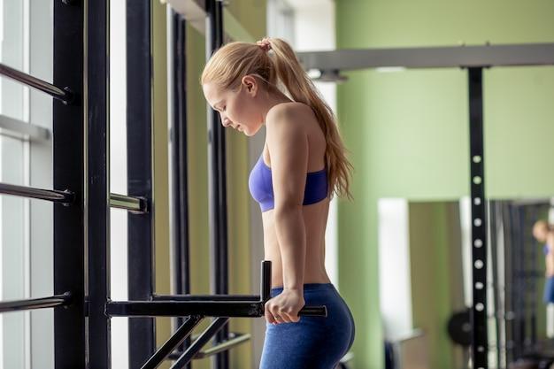 Parallette frau parallel bars workout-übung im fitnessstudio