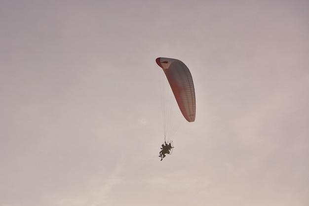 Paramotor (angetriebener gleitschirm) mit dem rot-weißen fallschirm, der in himmel, extremer sport fliegt.