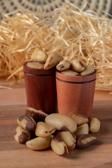 Paranüsse auf einem holztisch und in einer hölzernen tasse mit strohhintergrund. (castanha do brasil oder castanha do para)