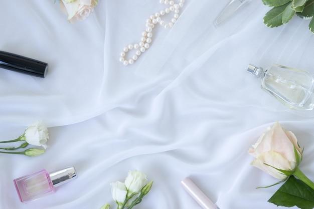 Parfüm, blumen, schmuck, perlen, kosmetik auf weißem chiffon-hintergrund. feminines elegantes modekonzept. flach liegen.