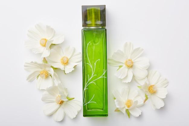 Parfüm für frauen in der grünen flasche und blumen herum lokalisiert auf weiß. angenehmer aroma oder geruch. blumenduft