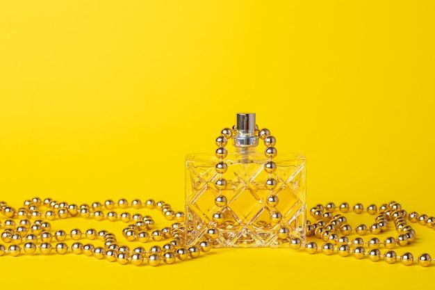 Parfüm für frauen in einer glasflasche an einer gelben wand. frauentoilettenwasser in einem transparenten flakon und goldperlen, festliche zusammensetzung, dekorationsdesign.