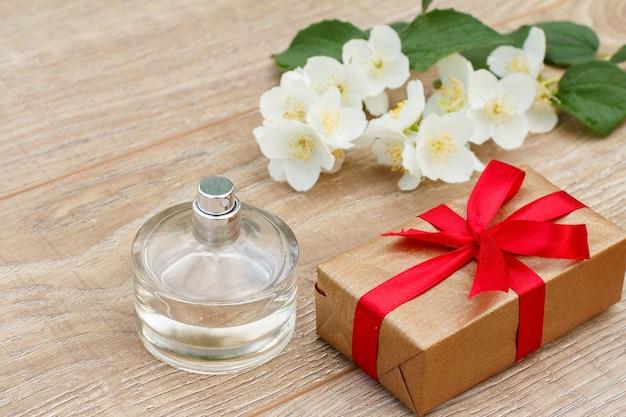 Parfüm, geschenkbox mit rotem band und jasminblütenzweig auf den holzbrettern. konzept, an feiertagen ein geschenk zu machen. ansicht von oben.