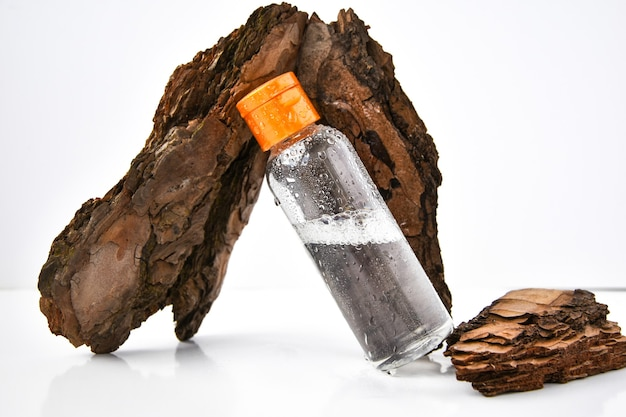 Parfüm in baumrinde mit wassertropfen. textur. konzept der frische und natürlichkeit. das aroma von holz und morgentau. herbstmelancholie. kopierraum, öl wird mit wasser in einer sprühflasche gemischt.
