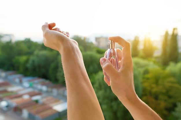 Parfüm in den händen bei abendsonnenuntergang