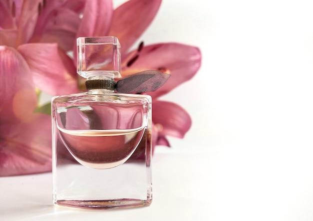 Parfüm mit blumen auf weißem hintergrund. eine parfümflasche, umgeben von lilienblüten in rosa und weißer farbe. eau de toilette, eau de parfum, beauty-konzept.