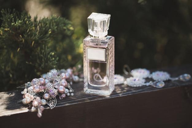 Parfüm und elegante hochzeitsdekorationen auf einem hölzernen hintergrund.