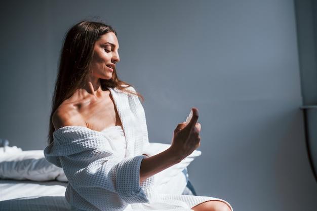 Parfüm verwenden. porträt einer schönen brünette in weißer kleidung, die auf dem bett im zimmer sitzt. schöne beleuchtung.