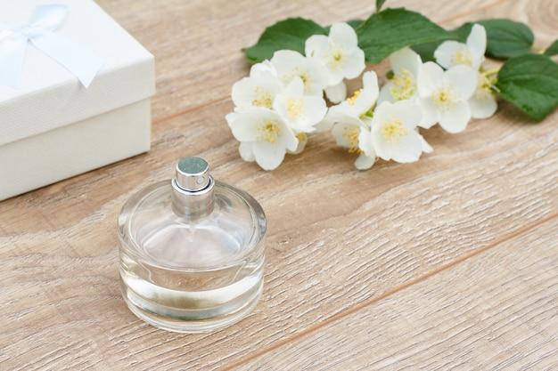 Parfüm, weiße geschenkbox und jasminblütenzweig auf den holzbrettern. konzept, an feiertagen ein geschenk zu machen. ansicht von oben.