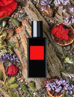 Parfümflasche auf natürlichem hintergrund aus baumrinde, blumen und steinen, draufsicht. schönheit und mode, parfümvorlage