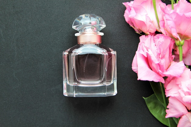 Parfümflasche der vorderansicht mit rosa rosen
