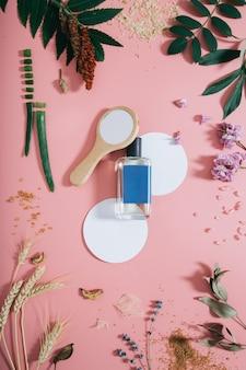 Parfümflasche in den blumen auf rosa wand mit weißer kreisform und spiegel. frühlingswand mit aroma-parfüm. flach liegen