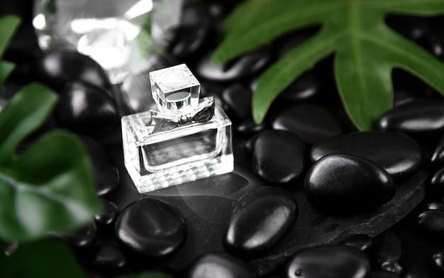 Parfümflasche mit frischen grünen blättern und schwarzem stein