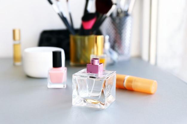 Parfümflasche mit make-up-werkzeugen und kosmetika auf einem tisch