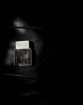 Parfümflasche. mockup auf dunklem oder schwarzem grungy hintergrund. duft für den mann. ansicht von oben.