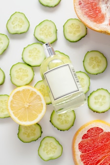 Parfümflasche, verziert mit rosenblättern, gurkenscheiben und zitrone mit saftiger grapefruit, auf weißem raum, draufsicht. das konzept der inhaltsstoffe oder der zusammensetzung von parfümölen