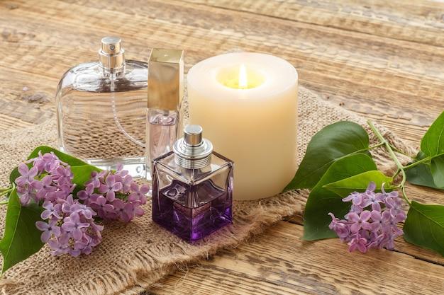 Parfümflaschen, eine brennende kerze und lila blumen auf sackleinen und alten holzbrettern.