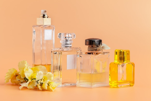 Parfümflaschen mit den blumenblumenblättern auf beige