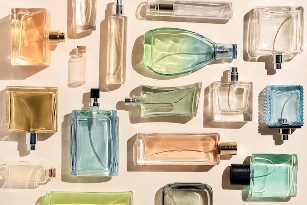 Parfümflaschen viele transparente mehrfarbige glasflaschen mit kosmetika auf beigem hintergrund und...