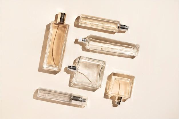 Parfümflaschen von beiger farbe. flatlay-stillleben im stil des minimalismus auf cremefarbenem hintergrund, schönheit und mode.