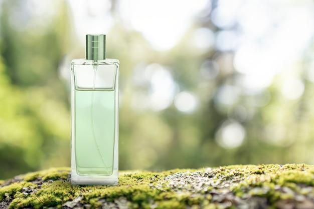 Parfümglas transparentes flaschengrünes modell auf dem hintergrund eines grünen waldes steht auf einem stein ...