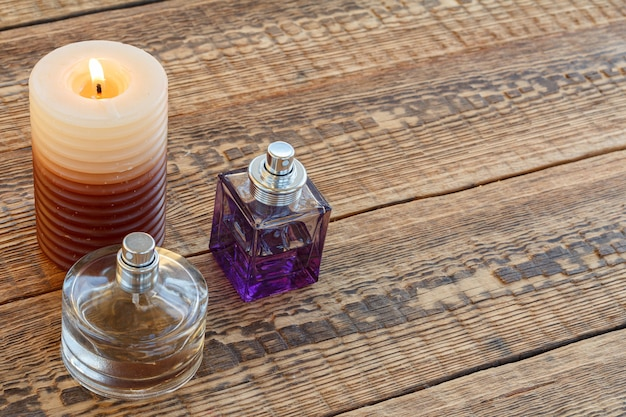 Parfüms und eine brennende kerze auf den alten holzbrettern. ansicht von oben. urlaubskonzept.