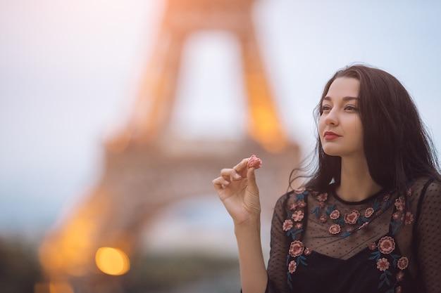 Pariser frau lächelnd, die das französische gebäck macaron in paris gegen eiffelturm isst.