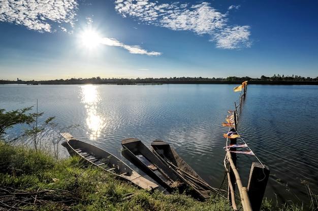 Park mit drei booten am seeufer im sonnenaufgang