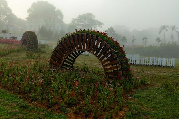 Park mit einem bogenförmigen pflanzenhalter und bunten blumen in phu yen, vietnam