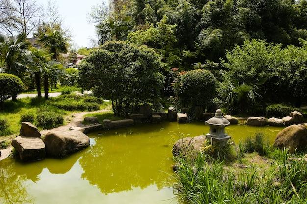 Park mit seeteich und felsen im japanischen stil, asiatische kultur. ruhige landschaft mit grüner vegetation.