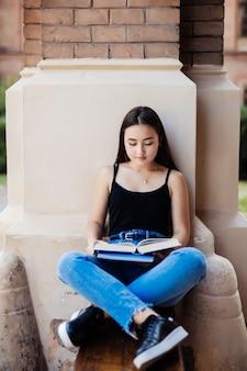 Parkfrau liest buch auf bank, die glücklich an der kamera lächelt. hübsche junge multikulturelle frau, die frühling im park genießt.
