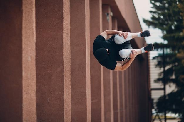 Parkour junger mann macht akrobatischen trick und springt hoch