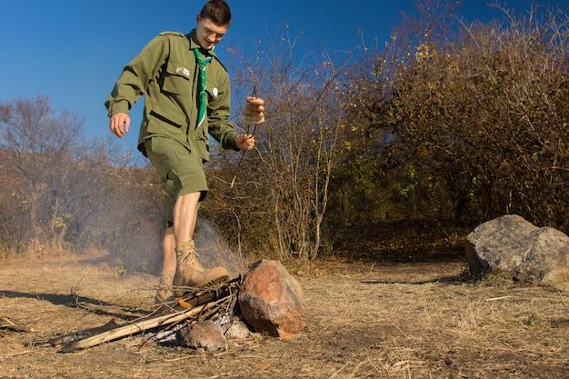 Parkranger oder pfadfinder, der mit seinem gestiefelten fuß ein kochfeuer ausstößt, nachdem er würstchen für sein mittagessen gekocht hat