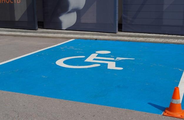 Parkschild auf dem asphalt, das einen platz für behinderte menschen mit einer waffe anzeigt