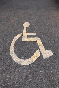 Parkschild für behinderte auf dem asphalt. vertikales foto