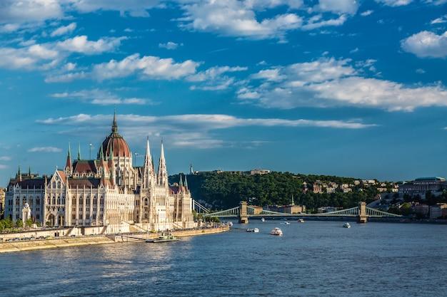 Parlament und flussufer in budapest ungarn mit besichtigungsschiffen während des sonnigen sommertages mit blauem himmel und wolken