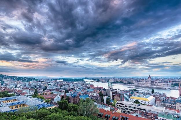 Parlament und flussufer in budapest ungarn mit drastischem himmel während des sonnenuntergangs