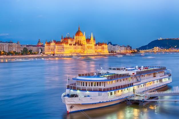 Parlament und flussufer in budapest ungarn mit während des blauen stundensonnenuntergangs