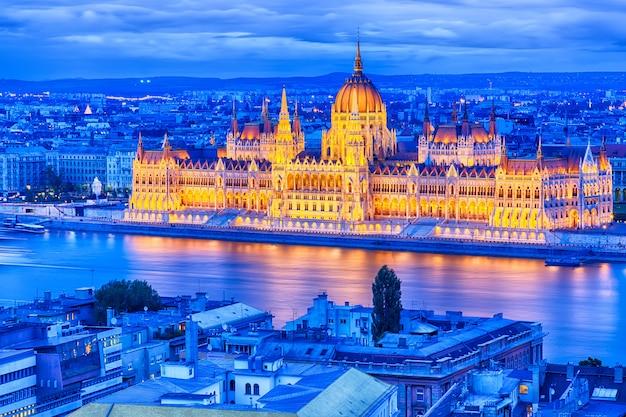 Parlament und flussufer in budapest ungarn während des blauen stundensonnenuntergangs