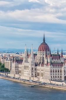 Parlament und flussufer in budapest ungarn während des sonnigen sommertages mit blauem himmel und wolken