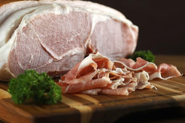 Parmaschinken in geschnittener nahaufnahme auf holzbrett