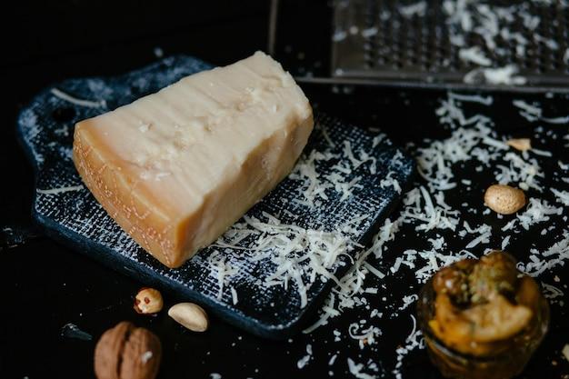 Parmesan käse. italienischer geriebener parmesankäseparmesankäse auf schneidebrett