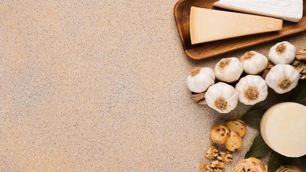 Parmesan käse; knoblauchknollen spanischer manchego-käse über strukturierter oberfläche mit platz für text