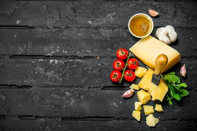 Parmesan mit tomaten, knoblauch und olivenöl. auf schwarzem rustikalem hintergrund.
