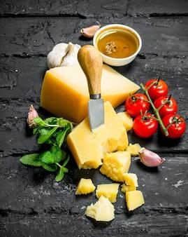 Parmesankäse mit tomaten, knoblauch und olivenöl auf schwarzem rustikalem tisch.