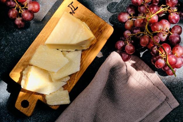Parmigiano-käse auf hölzernem schnittbrett mit traubenbeeren