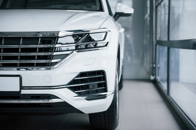 Partikelansicht des modernen weißen luxusautos, das tagsüber drinnen geparkt wird